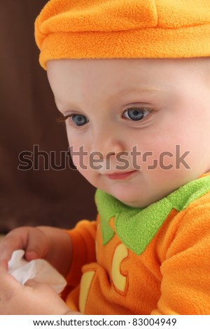 Baby boy in a pumpkin costume against brown background - stock photo