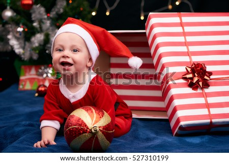 Baby boy in a santa outfit busy crawling out of a gift wrapped box as a present under the christmas tree, along with the other gifts and decorations.