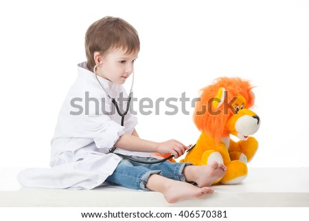 Baby boy in a white robe doctor makes an injection syringe toy lion cub . Isolated on white background - stock photo