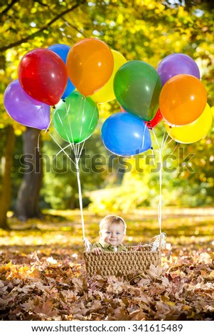 Baby boy in balloon basket - stock photo