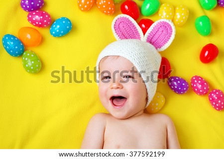 Baby boy in bunny hat lying on yellow blanket with easter eggs - stock photo