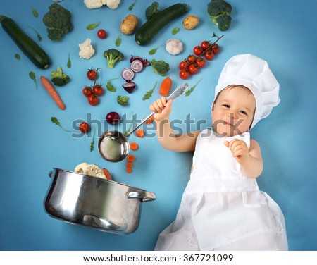 Baby boy in chef hat with cooking pan and vegetables - stock photo