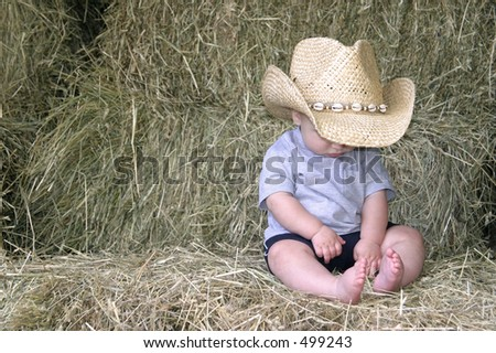 baby boy in cowboy hat sitting on hay bales - stock photo