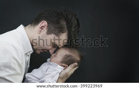 Baby Boy in Dad's Hands Black Background - stock photo