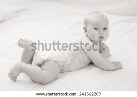 baby boy in diaper on his stomach looking into the camera - stock photo