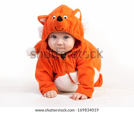 Baby boy in fox costume looking at camera over white - stock photo