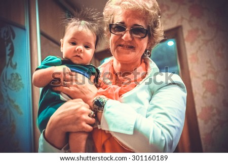 Baby boy in grandma's hands. Woman holding the baby and smiles - stock photo