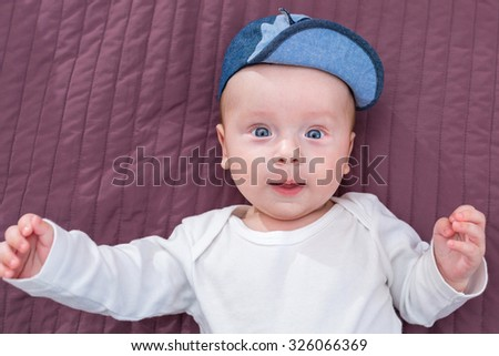 Baby boy in hat posing at the camera - stock photo