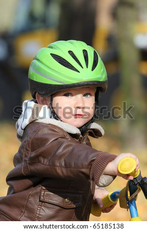 Baby boy in helmet learning to ride on bike