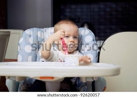 Baby boy in high chair eating yoghurt cream - stock photo