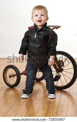 Baby boy in leather jacket in front of tricycle. - stock photo