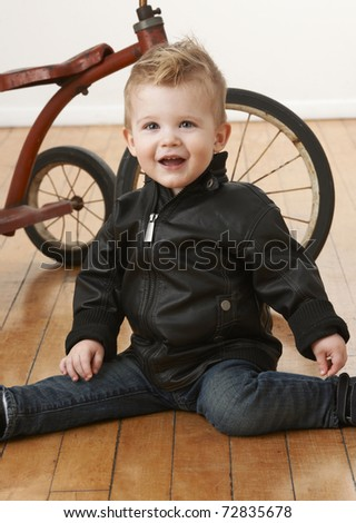 Baby boy in leather jacket sitting on floor in front of vintage tricycle. - stock photo