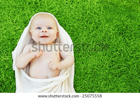 Baby boy in natural cotton cloth resting on green grass, space for text - stock photo