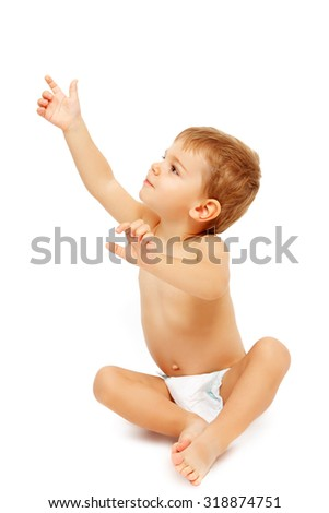 Baby boy in pampers pointing up, isolated on white - stock photo