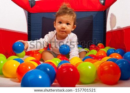 Baby boy in playpen playing with balls - stock photo