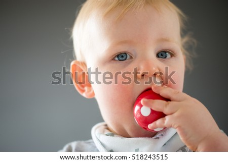 Baby boy in profile eating a ball toy as he learns through play