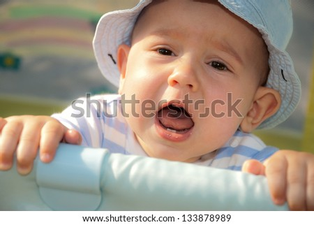 Baby boy in the blue hat crying, standing in a crib, with two of the tooth in his mouth - stock photo