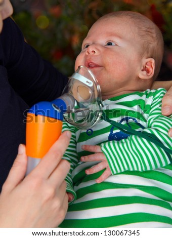 Baby boy in the mask of the inhaler - stock photo
