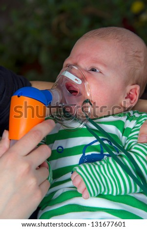 baby boy in the mask the inhaler - stock photo