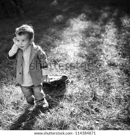 baby boy in the park talking on phone - stock photo