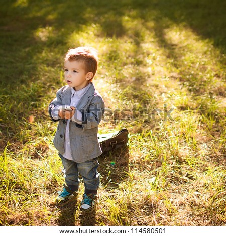 baby boy in the park talking on phone