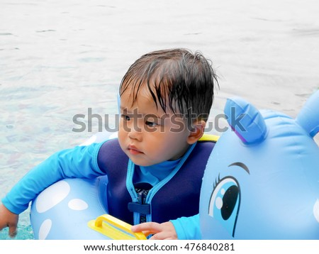 Baby boy in the swimming pool with inflatable ring
