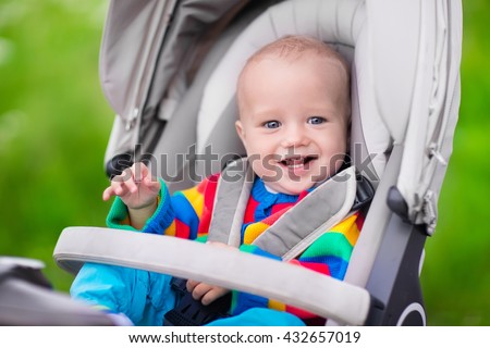 Baby boy in warm colorful knitted jacket sitting in modern stroller on a walk in a park. Child in buggy. Little kid in a pushchair. Traveling with young kids. Transportation for family with infant. - stock photo