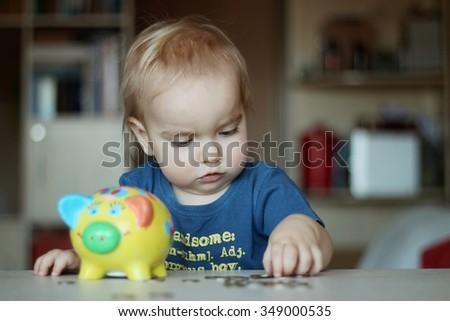 Baby boy inserting a coin into a piggybank, indoor financial concept - stock photo
