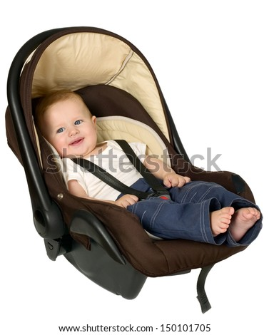 Baby boy is sitting in safety car seat - stock photo
