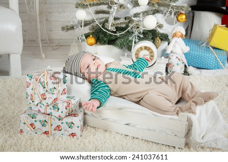 Baby boy laying in the box near x-mas tree - stock photo