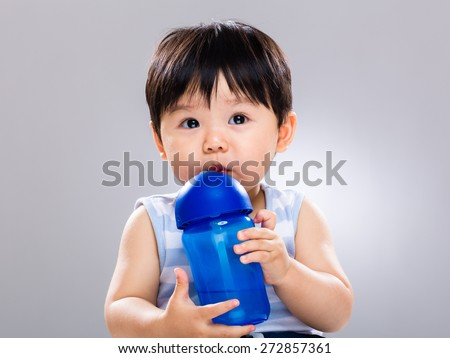 Baby boy learn to use water bottle for drinking - stock photo