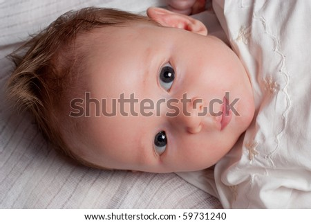 Baby boy lie on white diaper and look - stock photo