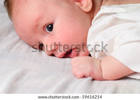 Baby boy lie on white diaper and look, close-up portrait - stock photo