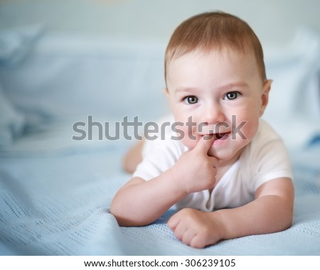 Baby boy lies on a stomach looks in the camera and smiles, blue blurring background
