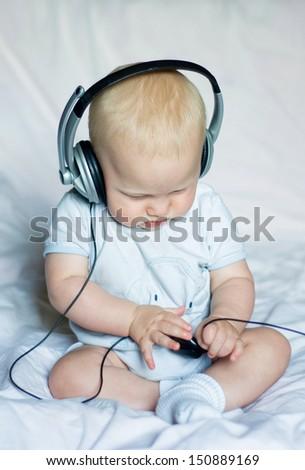 Baby boy listening to music - stock photo