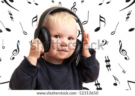 Baby boy listening to music surrounded with musical notes - stock photo