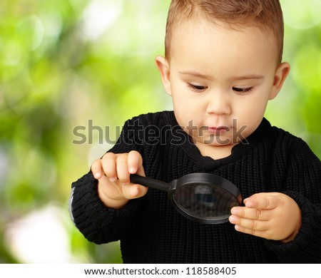 Baby Boy looking at Magnifying Glass against a nature background - stock photo