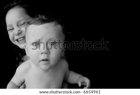Baby Boy Looking Serious with Laughing Sister Behind Him - stock photo