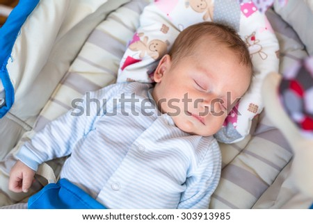 Baby boy lying down in the cradle - stock photo