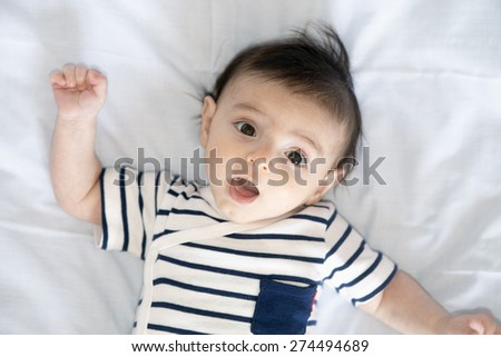 baby boy lying in the crib while playing, seen from above - stock photo