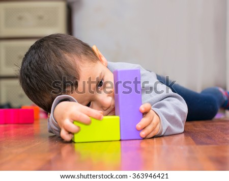 baby boy lying on the floor and plays with the figurines indoor - stock photo