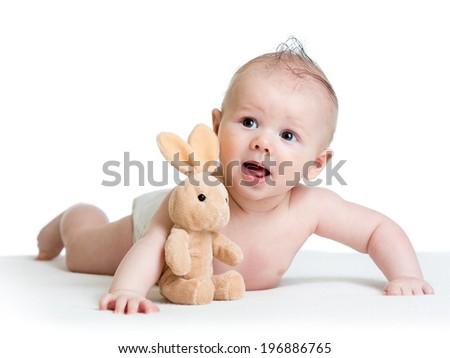baby boy lying on tummy with bunny toy - stock photo
