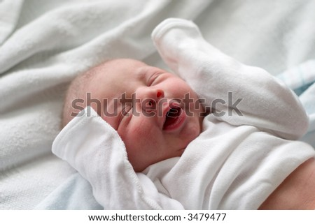 Baby boy making funny faces while sleeping - stock photo