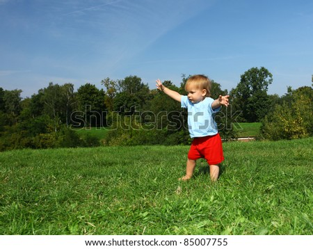 baby boy making his first steps on the meadow, series - stock photo