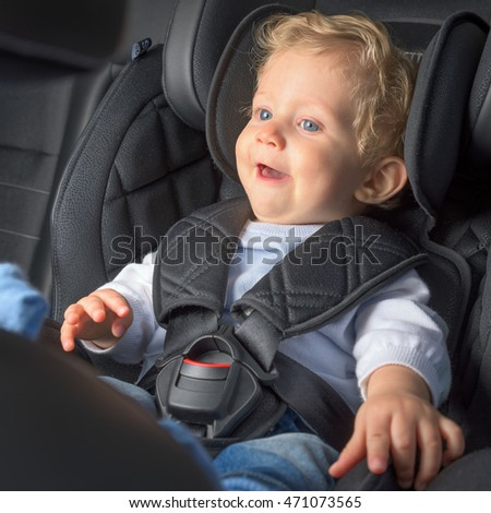 Baby boy 8 months old smiling in a safety car seat.