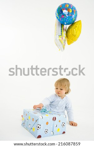 Baby boy (6-9 months) with baloons and present - stock photo
