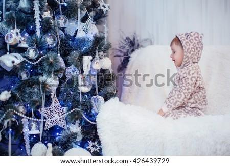 Baby boy near Christmas tree - stock photo
