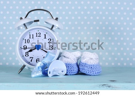 Baby boy nursery blue and white booties and clock, on aqua vintage shabby chic wood table and polka dot background for baby shower or newbornl greeting card. - stock photo