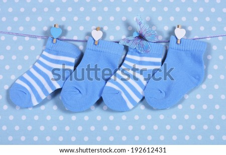 Baby boy nursery blue socks and butterfly hanging from pegs on a line against a blue polka dot background for baby shower or newborn greeting card. - stock photo