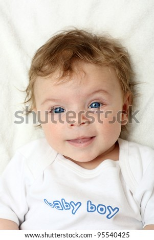 Baby boy on white blanket smiling. - stock photo